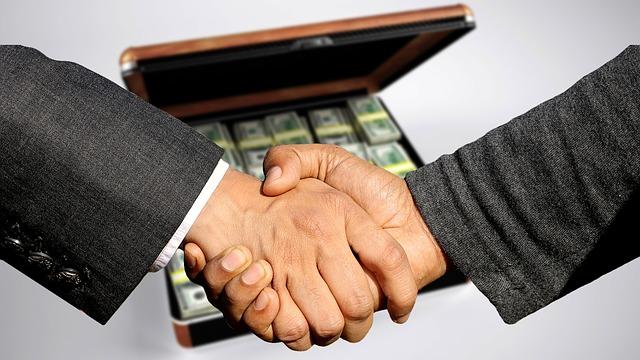 podané ruce nad kufrem plným peněz.jpg