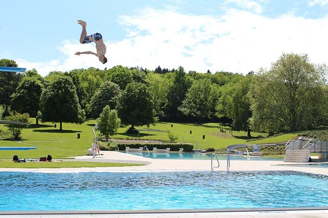 muž skákající do bazénu